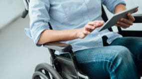 Unrecognizable woman in wheelchair using a digital touch screen tablet, disability and assistance concept