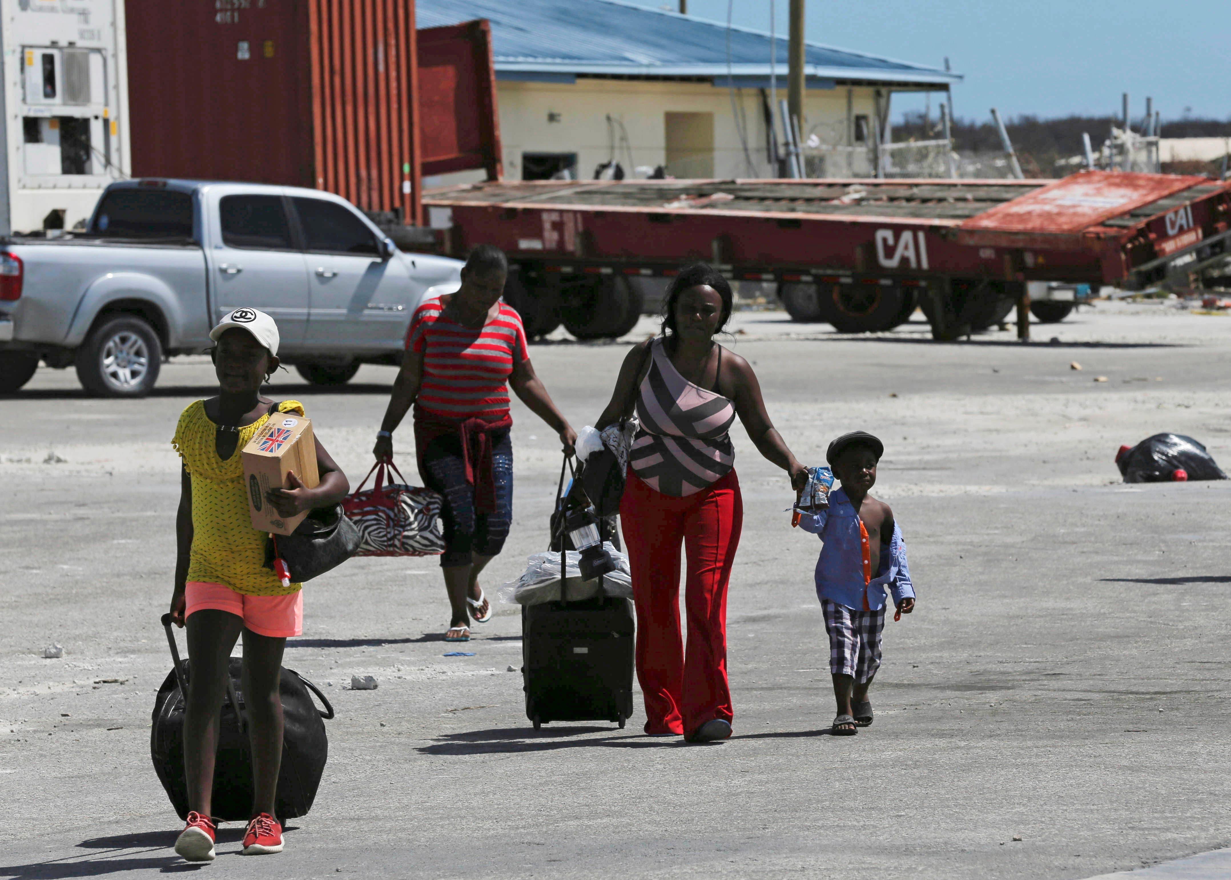 Evacuados cargando sus pertenencias camino de un transbordador para salir de Nassau tras el huracán Dorian, en el puerto de Marsh Harbor, en la Isla Ábaco, Bahamas, el domingo 8 de septiembre de 2091. (AP Foto/Fernando Llano)