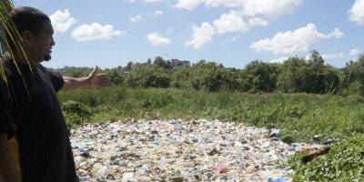 """José Núñez  señala  el """"mar de basura"""" que se acumula en  los patios de las viviendas  .  e. tapia"""