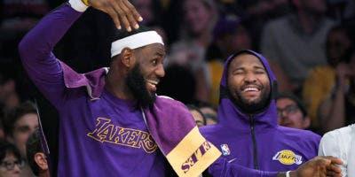 El alero de Los Angeles Lakers, LeBron James, a la izquierda, bromea con el centro DeMarcus Cousins en el banco durante la segunda mitad del juego de baloncesto de la NBA de pretemporada del equipo contra los Golden State Warriors el miércoles 16 de octubre de 2019 en Los Ángeles. AP