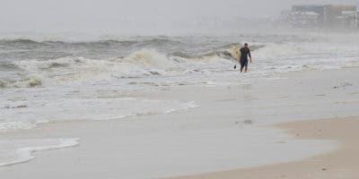 Un surfista regresa de surfear las altas olas en la playa de México, Florida, después de que la tormenta tropical Néstor azotara la ciudad el sábado 19 de octubre de 2019.