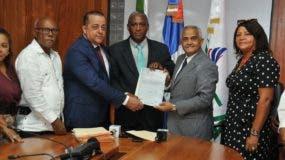 El ministro de Agricultura, Osmar Benítez y el director del CEA, Luis Manuel Piccirillo entregan un título al presidente del ANPA, Juan Marte Peña.