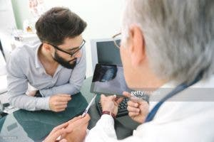 Mature doctor using a digital tablet for his diagnosis.