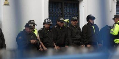 Policías permanecen tras las vallas que cierran una calle este domingo, en el centro de Quito (Ecuador). A pie o aglutinados en las tolvas de las camionetas, los ecuatorianos desafiaron este domingo el toque de queda decretado en la víspera por el Gobierno y volvieron a salir a las calles de Quito para manifestarse por miles en El Arbolito, el parque del centro convertido ya en un emblema desastroso de las protestas. EFE