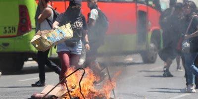 Una manifestante enciende una barricada este martes en una calle de Valparaíso (Chile). Miles de personas en Chile volvieron a salir a la calle este martes, por quinto día consecutivo, para protestar contra el Gobierno en medio de los estados de emergencia y los nuevos toques de queda ya decretados en varias zonas del país. EFE