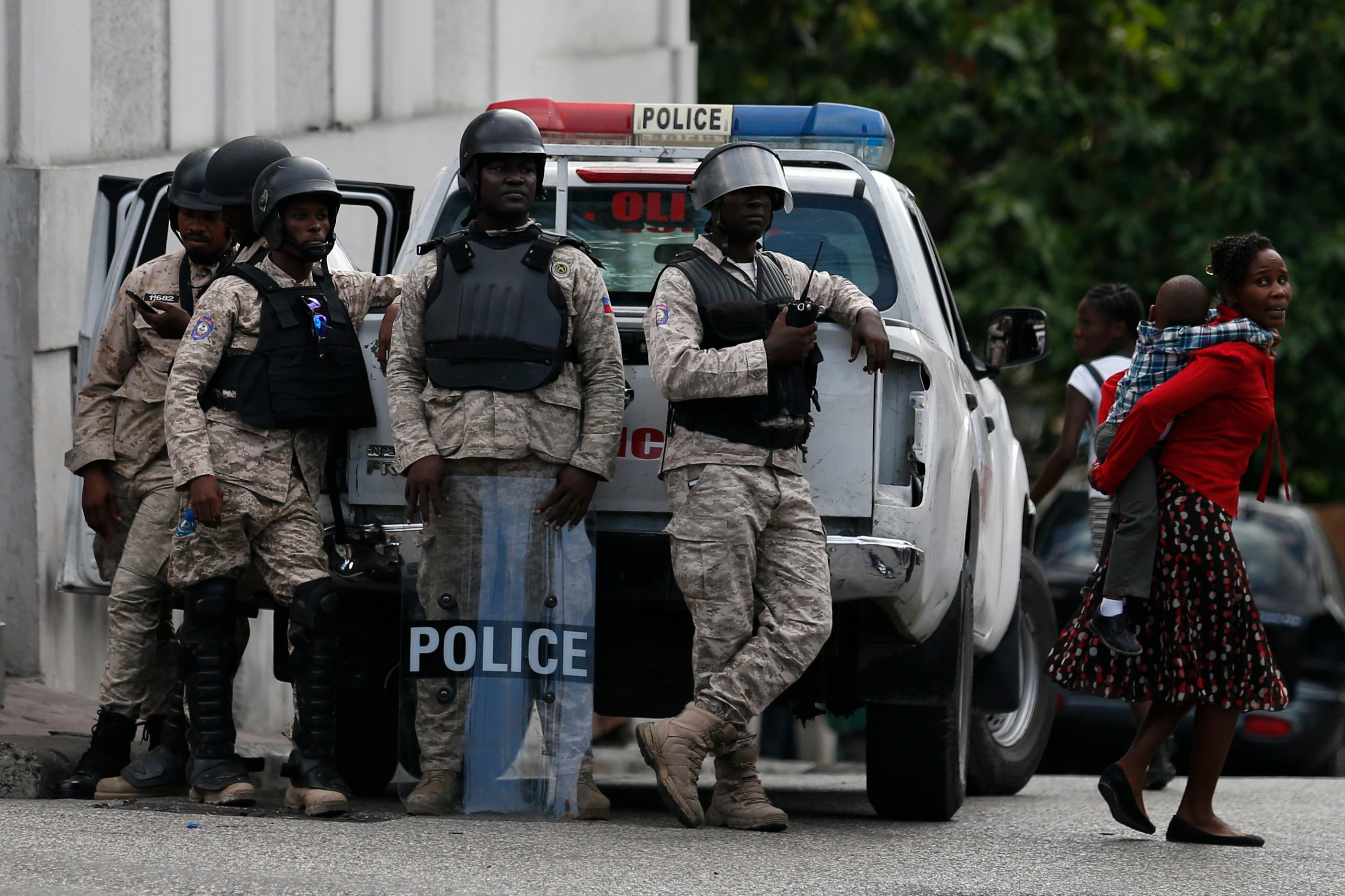 Una mujer lleva a un niño pasando la guardia policial durante una protesta liderada por la comunidad artística que exige la renuncia del presidente haitiano Jovenel Moïse, en Petion-Ville, Puerto Príncipe, Haití.