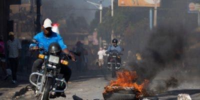 Un hombre conduce su moto por una calle bloqueada por barricadas en llamas durante una jornada de protestas este jueves, en Puerto Príncipe (Haití). EFE