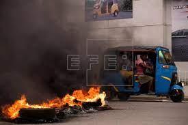 Un taximoto con algunas pasajeras pasa junto a una barricada en llamas, durante una jornada de protestas, hoy, en Cap-Haitien (Haití). EFE/Orlando Barría