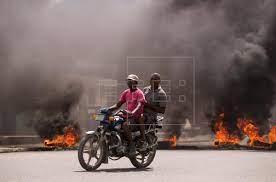 Dos hombres en motocicleta pasan junto a una barricada en llamas durante una jornada de protestas, hoy, en Cap-Haitien (Haití). EFE/Orlando Barría